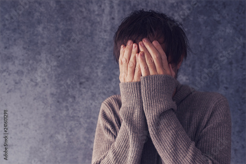 Crying man with face in hands