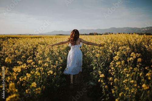 Rear view of woman in white dress walking in field - 241605259