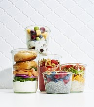 Jars With Food And Vegetable Against White Background