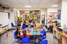 Children And Teacher Eating Lunch In A Classroom