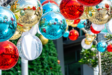 Shiny Xmas Glass Baubles Ball Hanging On Fir Over Colorful Bokeh With Festive. Christmas Bauble Twinkling Light And Ornament On Colurful Glitter.Merry Christmas And Happy New Year Background.
