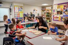 Teacher Helping Children With Their Classwork