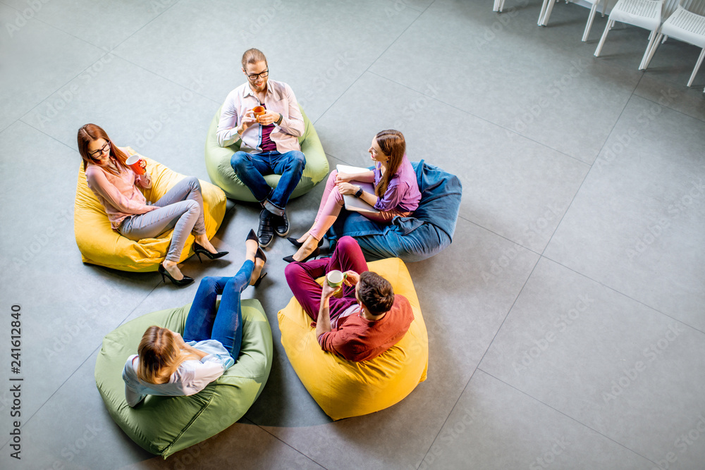 Fototapety, obrazy: Group of a young coworkers sitting together on the colorful poufs resting during the coffee break in the office, view from above