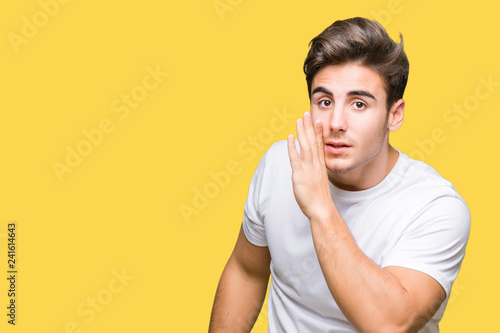 Young handsome man wearing white t-shirt over isolated background hand on mouth Canvas Print