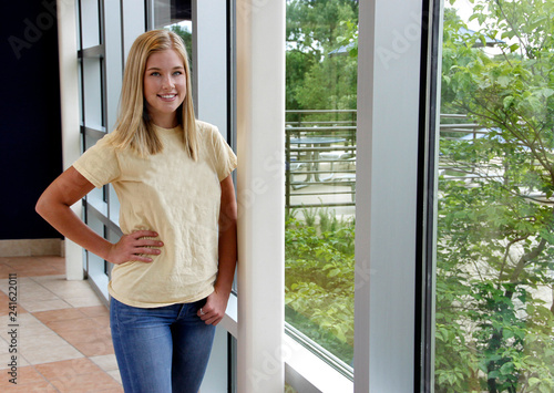 Fotografie, Obraz  Female college student standing next to wall of windows