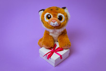 Toy Tiger Sits On A White Gift Box With A Red Ribbon On A Purple Background