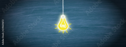 Light bulb in the middle of blue chalkboard background, copyspace for individual Canvas Print