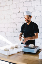 Smiling Chef Measuring Dough On Weight Scale Against Wall In Commercial Kitchen At Pizzeria