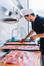 Chef Applying Pizza Sauce On D...