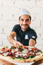 Portrait Of Smiling Chef With Cooked Pizza On Cutting Board In Pizzeria