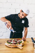Chef Pouring Sauce On Pizza In...