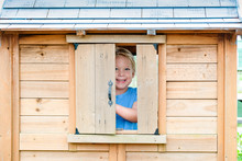 Portrait Of Smiling Girl Standing At Window In Wooden Playhouse