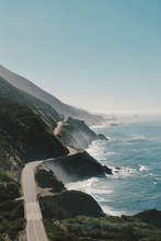 Scenic View Of Road On Mountains By Sea Against Clear Blue Sky