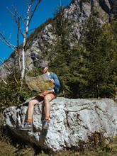 Full Length Of Hiker Reading Map While Sitting On Rock Against Mountain In Forest During Sunny Day