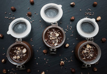 Overhead View Of Chocolate Sauce In Jars With Nuts On Slate