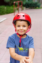 Portrait Of Cute Smiling Boy Wearing Red Sports Helmet Playing Hockey In Park