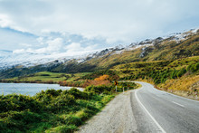 Long Winding Road Leading To A Snow Capped Mountain In New Zealand