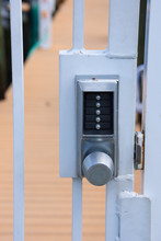 Locked Private Metal Security Gate Door With Pushbutton Combination Lock System Keypad With Metallic Silver Doorknob Handle.