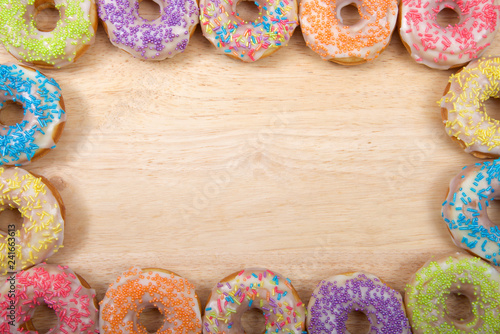 Flat lay view of many Frosted donuts with candy sprinkles arranged in a border frame on a light wood table with copy space.