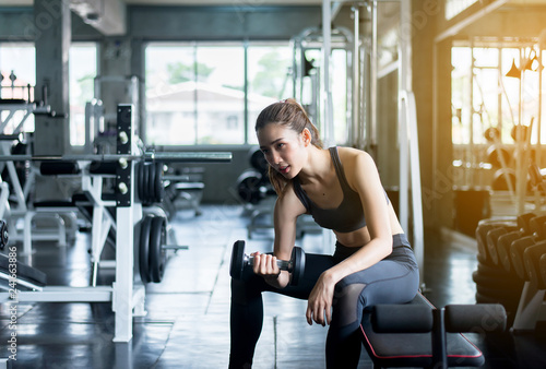 Foto  Sporty woman exercise with dumbbells,Female in sportswear does the exercises at