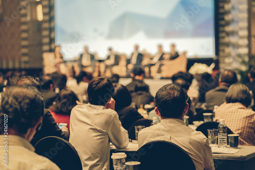 Fototapeta Rear view of Audience listening Speakers on the stage in the conference hall or