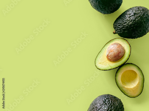 Fotografiet Fresh organic hass avocados on a green background, top view with copy space