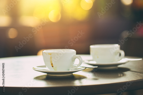 two coffee cups on wooden table in the morning cafe vintage tone.