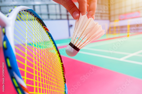 Photo close up hand hold serve badminton shuttlecock with blur badminton court backgro