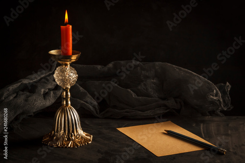 Fotografía  still life, burning candle on a gadget and a sheet of old paper with a pencil