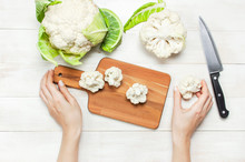 Female Hands Cut Cauliflower With Knife On Cutting Board, Kitchen Towel On Rustic White Wooden Background Top View Flat Lay Copy Space. Cooking, Healthy Wholesome Food, Vegetable, Diet Concept.