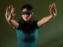 Young Scared And Blindfolded Asian Korean Teenager Girl Lost And Confused Playing Dangerous Internet Viral Challenge Isolated On Dark Background