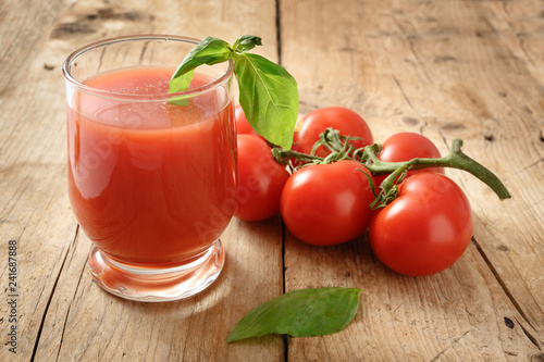 fresh organic tomato juice in a drinking glass with pepper and basil garnish on a rustic wooden board, healthy smoothie drink with copy space, selected focus, narrow depth of field