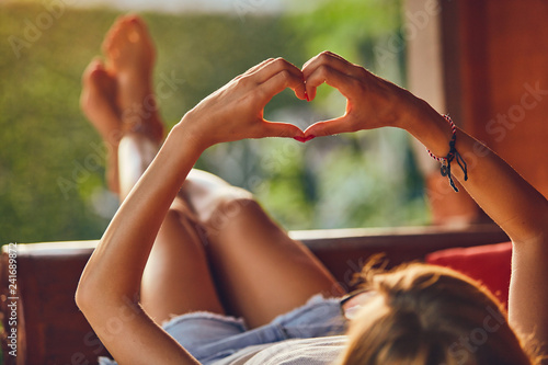 Fotografie, Obraz  Girl holding a heart-shape symbol while lying on the couch.