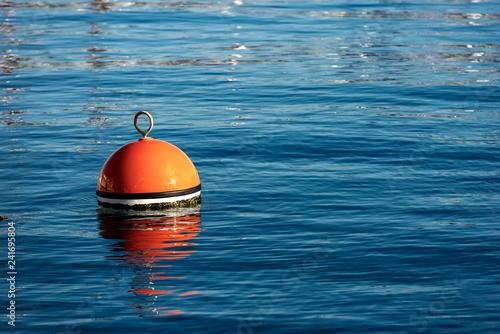Fototapeta Red and orange mooring buoy in the sea