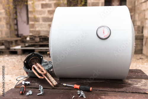 the heating element and the screwdriver with bolts lie on the background of the water heater