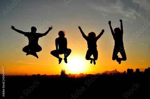 Siluetas de amigos en contraluz divirtiéndose en la puesta de sol Canvas Print