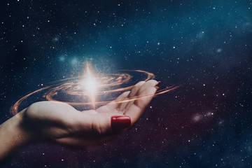 Woman hand hold a new star in infinite space. Mixed media.