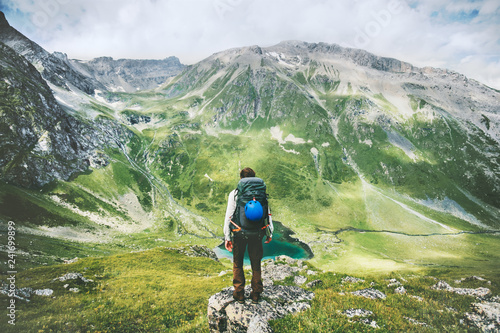 Obraz Traveler man hiking alone in mountains adventure active lifestyle traveling  summer vacations outdoor solitude harmony with nature hiker standing on cliff above lake landscape - fototapety do salonu