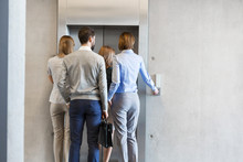 Rear View Of Business People Waiting For Elevator At Office