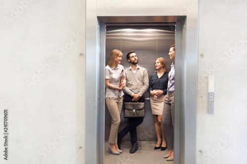 Colleagues talking while standing in elevator at office Wallpaper Mural
