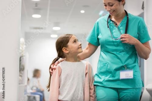 Carta da parati  Smiling girl looking at mid adult nurse while walking in hospital corridor