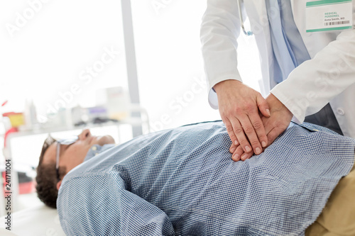 Doctor treating stomach of patient in examination room Canvas Print