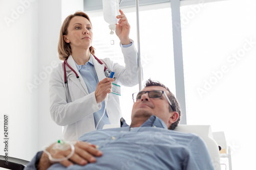 Mature doctor adjusting saline IV drip for patient in hospital ward Canvas Print