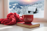 cup with a hot drink on the windowsill in the background of a winter city. Focus on the edge of the cup