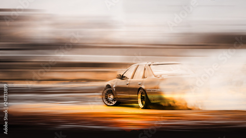 Double exposure sunset with car drifting, Blurred of image diffusion race drift car with lots of smoke from burning tires