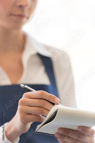 Fototapeta Midsection of young waitress writing on notepad at restaurant obraz na płótnie