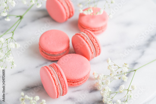 Foto op Canvas Macarons Coral cakes macarons or macaroons on white marble. The concept of Valentines day and spring's celebrating.