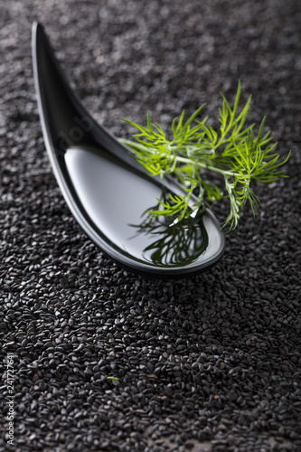 Plant oil with dill branches on a background of black sesame.
