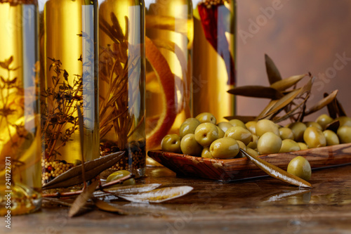 Green olives and bottles of olive oil .