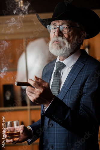 Fényképezés  Elegant senior gentleman wearing spectacles and grey-haired beard standing at pub in wide-brimmed hat with glass of alcohol drink and cigar